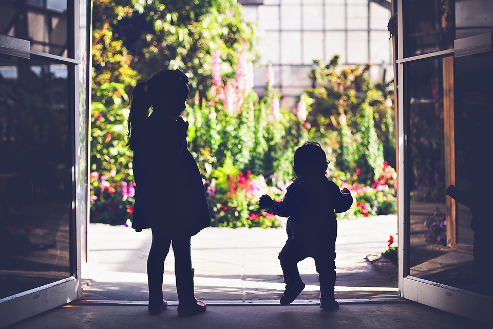 Sibling silhouette greenhouse flowers | Tonya Teran Photography, Potomac, MD newborn, baby and family photographer